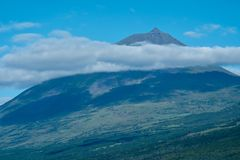 Portugal`s highest mountain is Mount Pico. Mount Pico towering 2350 metres over Pico Island in the Azores is a dormant volcano Royalty Free Stock Photo