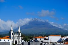 The town of Madalena on Pico Island. Mount Pico volcano seen towering over the town of Madalena on Pico island in the Azores royalty free stock photo