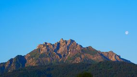 Mount Pilatus in the early morning with cloudless sky and the setting moon stock photo