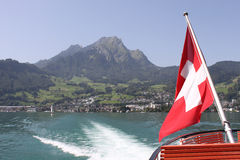 Mount Pilatus with Swiss Flag and wake of boat. Stock Photo