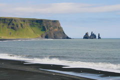 Mount Reynir and Reynisdrangar. Mount Reynir and rock formations of Reynisdrangar from the Dyrholaey promontory in the southern coast of Iceland stock images