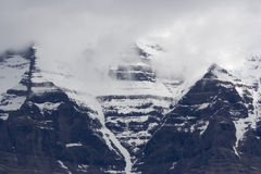 Mount Robson with snow and peak in clouds Royalty Free Stock Image