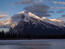 Mount Rundle, Banff Alberta. Mount Rundle reflected in the icy waters of Vermilion Lakes near Banff Alberta Canada at sunset Stock Photo
