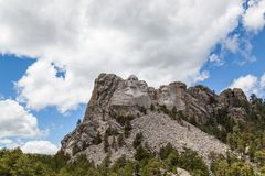 Mount Rushmore. Blue sky and white fluffy clouds provide a striking back drop for the carved faces of four famous United States Presidents in Mount Rushmore stock photography