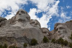 Mount Rushmore. Blue sky and white fluffy clouds provide a striking back drop for the carved faces of four famous United States Presidents in Mount Rushmore stock images