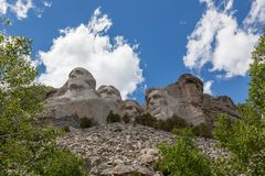 Mount Rushmore. Blue sky and white fluffy clouds provide a striking back drop for the carved faces of four famous United States Presidents in Mount Rushmore stock photos