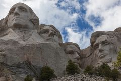 Mount Rushmore Close Up. Blue sky and white fluffy clouds provide a striking back drop for the carved faces of four famous United States Presidents in Mount stock images