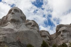 Mount Rushmore Close Up. Blue sky and white fluffy clouds provide a striking back drop for the carved faces of four famous United States Presidents in Mount royalty free stock images