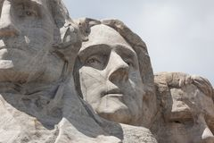Mount Rushmore Close Up. Sunshine and white clouds provide a striking back drop for three of the carved faces of famous United States Presidents in Mount royalty free stock photo