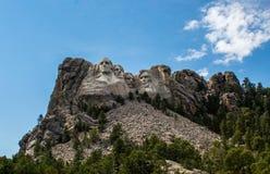 Mount Rushmore med mestadels klar blå himmel med några vita moln Arkivbild