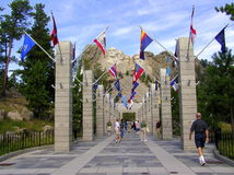 Mount Rushmore Memorial and Avenue of Flags. The Mount Rushmore National Memorial visited by nearly three million people each year that come to marvel at the Royalty Free Stock Photo