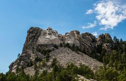 Mount Rushmore with mostly Clear Blue Sky with some White Clouds.  Stock Photography