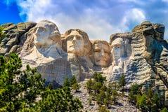 Mount Rushmore som är molnigt med blåa himlar arkivfoton