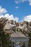 Mount Rushmore with State Flags. The four presidential heads of Mount Rushmore lit by spring sunshine with a display of state flags through the walkway below stock image