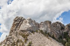 Mount Rushmore in Sunshine. Sunshine, blue sky and white clouds provide a striking back drop for two of the carved faces of famous United States Presidents in stock photo