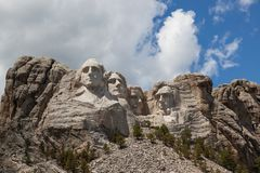 Mount Rushmore in Sunshine. Sunshine, blue sky and white clouds provide a striking back drop for the carved faces of four famous United States Presidents in royalty free stock images