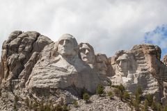Mount Rushmore in Sunshine. Sunshine, blue sky and white clouds provide a striking back drop for two of the carved faces of famous United States Presidents in royalty free stock photography