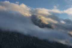 Mount Sass de Stria at sunrise, blue sky with clouds and fog, Falzarego pass, Dolomites, Veneto, Italy Stock Photo