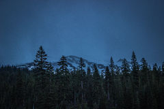 Mount Shasta at night with forest in foreground Stock Photo