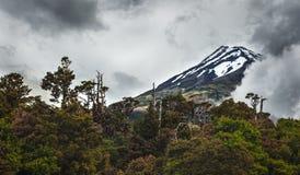 Mount Taranaki, New Zealand perfect volcano mountain. Snowy Mount Taranaki in the North Island of New Zealand. It is one of the 4 prominent volcanoes of the Stock Photos