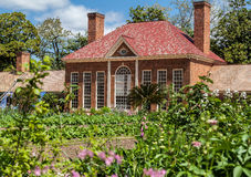 Mount Vernon Greenhouse Washington. The brick building with chimneys of the greenhouse in Mount Vernon, Virginia and the garden with blooming flowers Stock Image