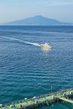 Sorrento, summer afternoon. View of Mount Vesuvius and Naples bay with people bathing and taking sun in Sorrento. A boat is coming to the harbor from Capri stock photo
