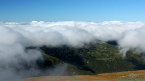 Mount Washington peak stands above a thick layer of fluffy clouds. In New Hampshire stock video footage