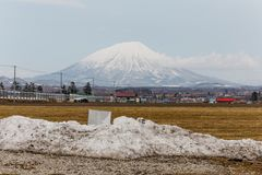 Mount Yotei inactive stratovolcano with village on the foot hill and yellow grass on the ground with pile of snow on foreground Royalty Free Stock Images