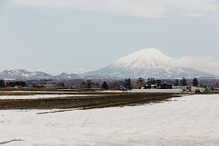 Mount Yotei inactive stratovolcano with village and snow cover on the ground in winter in Hokkaido, Japan Stock Images