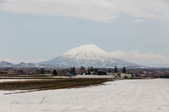 Mount Yotei inactive stratovolcano with village and snow cover on the ground in winter in Hokkaido, Japan Stock Image