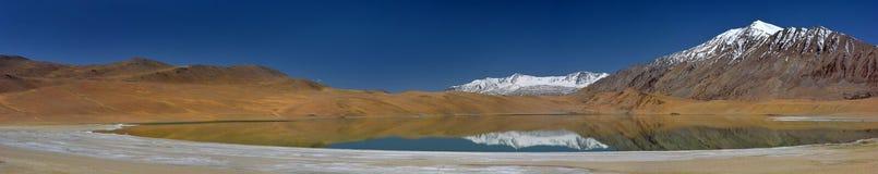Mountain小湖,水光滑的表面上在镜子褐色山被反射,上面用雪报道和 免版税库存照片