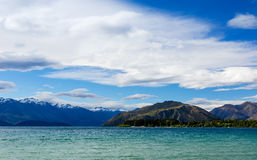 Mountain湖在蓝色多云天空下 免版税库存图片