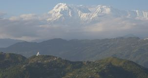 Mountain above the clouds. Paradise on Earth, Himalayan mountain higher than the clouds. Snow covered rocks rise up to the sky from clouds over forest hills and stock video