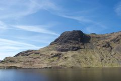 Mountain above still, clear tarn lake on a sunny day stock image