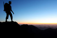 Mountain adventure. Silhouette of a man in the mountains at dawn Stock Image
