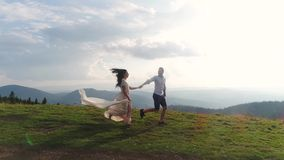 Mountain adventure. Man and woman in long white dress run over the hill in the rays of sun. 4k.  stock video footage