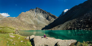 Mountain Alpine lake and a girl sitting on the stone. Panorama of mountain Alpine lake and a girl sitting on the stone Royalty Free Stock Images