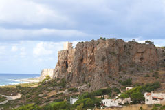 Mountain with an ancient tower overlooking the ocean Cala Macari Sicily, Italy Stock Image