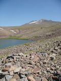 Mountain of the Aragats  with a small lake in Armenia. Mountain of the Aragats with a small lake in Armenia. Blue clear sky. Sunny day. Stones in foreground Stock Image