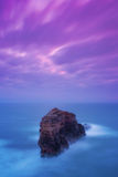 Mountain as a fortress on the sea in stormy sea and pink sky. Stock Image