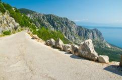 Mountain asphalt road on the top of peak Sveti Jure in front of hills and rocks of Biokovo mountain range and Makarska riviera stock image