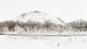 Mountain on a background of the ice river. Winter landscape in R Royalty Free Stock Photo