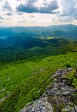 Mountain behind the valley viewed from rocky cliff. Beautiful summer landscape with grassy slopes under the cloudy sky. location mountain Pikui, TransCarpathia Stock Photo