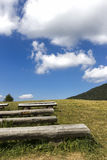 Mountain Benches. Wooden benches in a meadow in the mountains. Italy Stock Photo