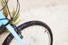 Mountain bicycle front wheel on road under the rain. Stock Photo