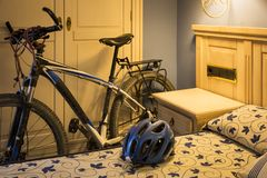 Mountain bicycle and a helmet in a hotel room - Bicycle touring. A mountain bicycle and a helmet in a hotel room - Bicycle touring royalty free stock image