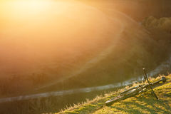 Mountain bicycle is on the hill with green grass on sunset background. Stock Photos