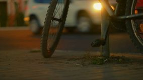 Mountain bicycle in night city. We can see blurred car traffic flow around. Low angle shot stock footage