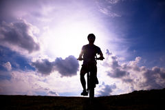 Mountain bicycle rider on the hill with sunrise background Stock Photo