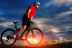 Mountain bicycle rider on the hill with sunrise background Stock Photos